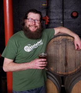 image of a man standing in front of a cask, holding a glass of beer